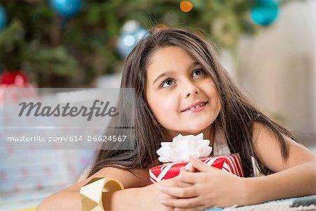 Girl holding Christmas present on floor