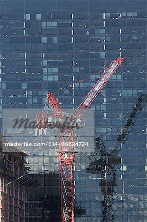 Crane by urban skyscraper