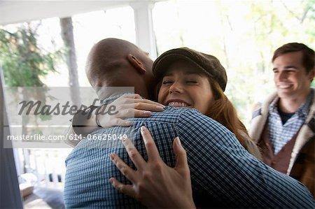 Friends hugging at front door
