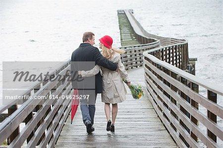 Couple walking on wooden dock