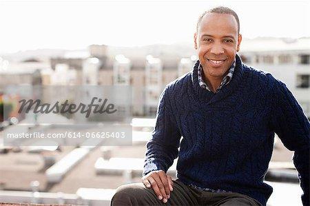 Smiling man sitting on urban balcony