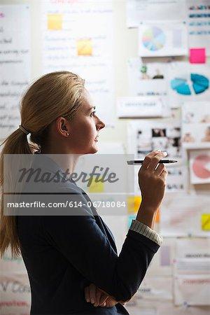Contemplative woman holding pen