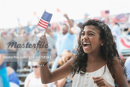 Girl cheering and waving american flag