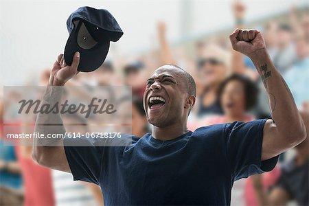 Man cheering at sports game, holding baseball cap