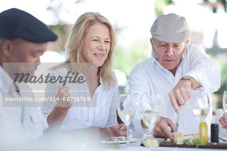 Older friends eating together outdoors