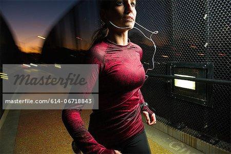 Woman running on pedestrian bridge