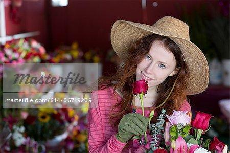 Florist smelling flowers in shop
