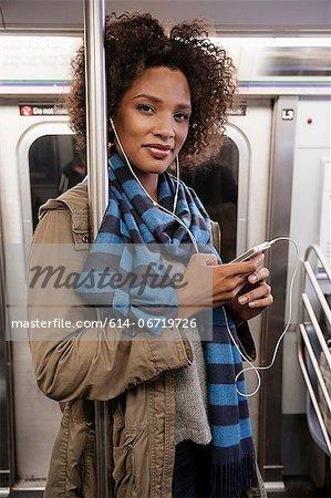 Woman listening to earphones on subway