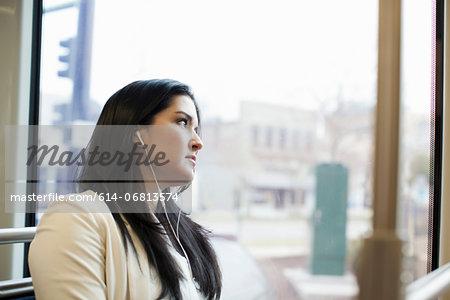 Young woman traveling on light train wearing earphones