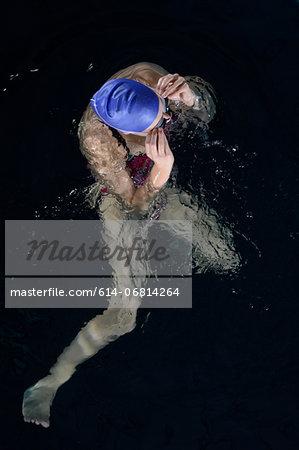 Teenage girl adjusting goggles in swimming pool