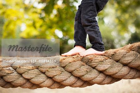 Male toddler crossing rope bridge