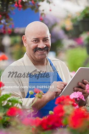 Mature man using clipboard in garden centre, portrait
