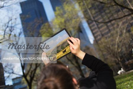 Woman in city park looking at digital tablet screen