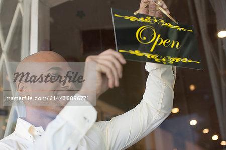 Shopkeeper turning open sign on vintage shop door