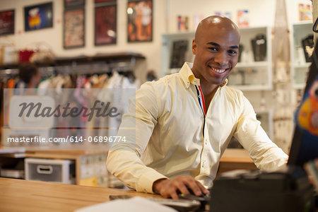 Shopkeeper using computer in vintage shop