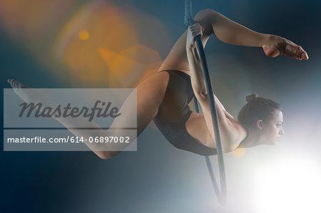 Side view of aerialist performing on hoop