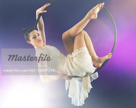Aerialist poised on hoop against purple background
