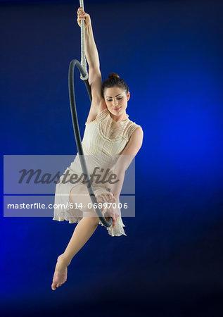 Aerialist poised on hoop against blue background