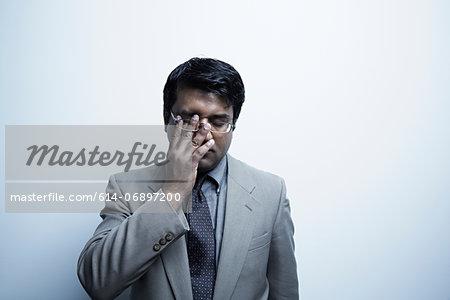 Studio portrait of businessman rubbing his eye