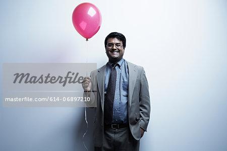 Studio portrait of businessman holding red balloon