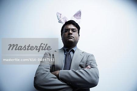 Studio portrait of businessman wearing bunny ears