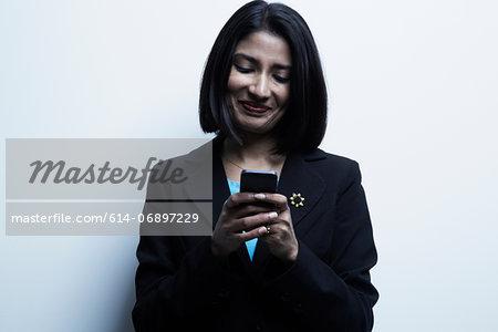 Studio portrait of businesswoman looking at cellphone