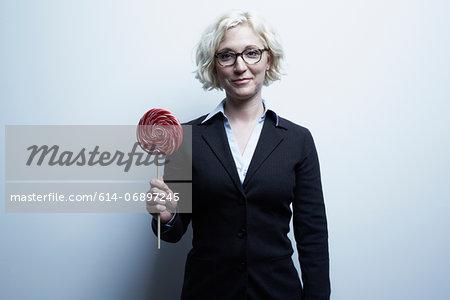 Studio portrait of blond businesswoman with red lollipop