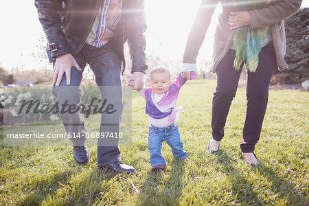 Grandparents walking granddaughter in garden