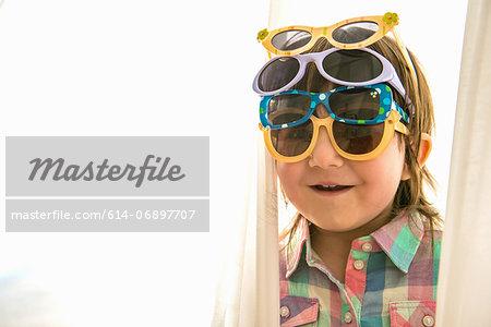 Girl wearing four paris of sunglasses