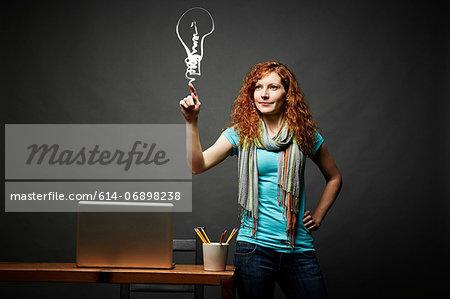 Woman drawing a light bulb