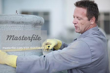 Factory worker measuring a large vase