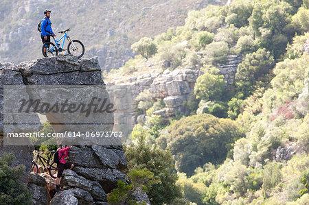 Mountain biking couple on rock formation looking ahead