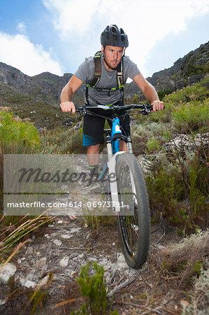 Young man mountain biking through mountains