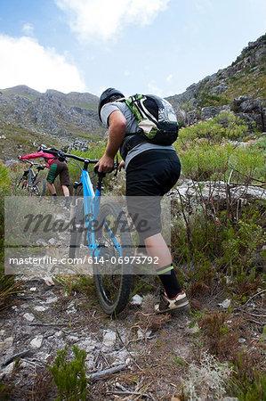 Young couple pushing mountain bikes up mountain path