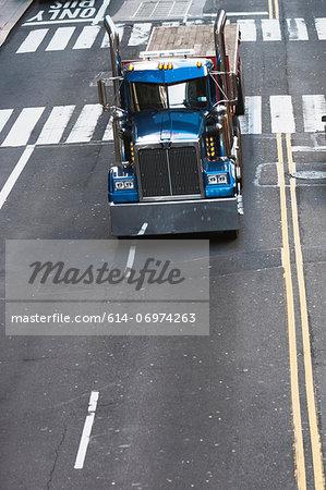 Blue truck driving on city street