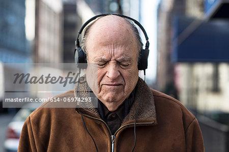 Senior man with eyes closed wearing headphones