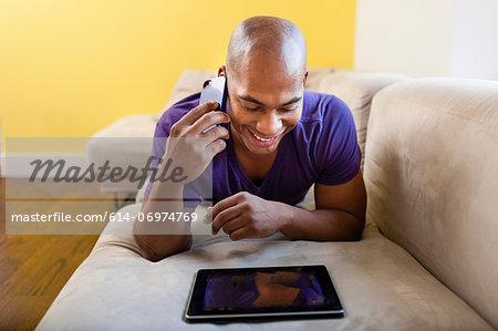Mid adult male on sofa using digital tablet and smartphone