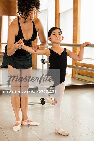 Mature woman teaching ballet dancers in studio