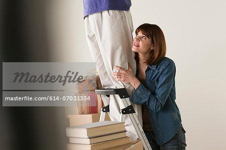 Woman holding onto man on stepladder
