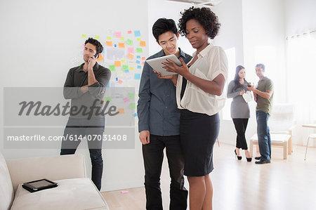 Office workers looking at digital tablet