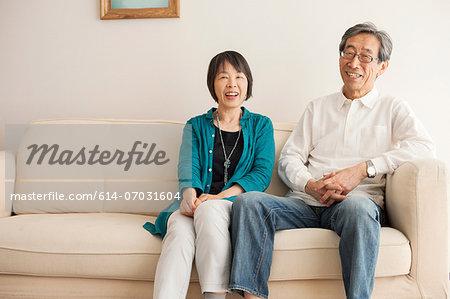 Senior couple sitting on sofa, portrait