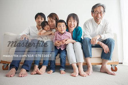 Three generation family sitting on sofa, portrait