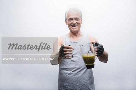 Senior man holding smoothie in blender, portrait