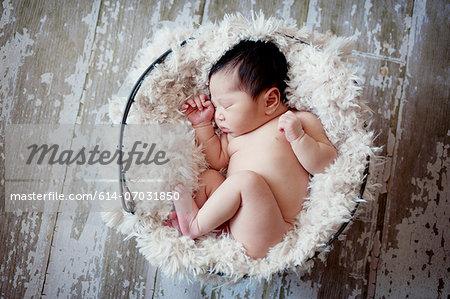Baby boy sleeping in fur lined basket