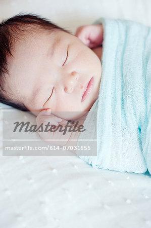 Baby boy wrapped in blanket sleeping