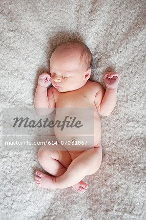 Baby boy's sleeping on blanket, overhead view