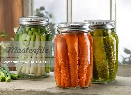 Three jars of pickled vegetables on windowsill
