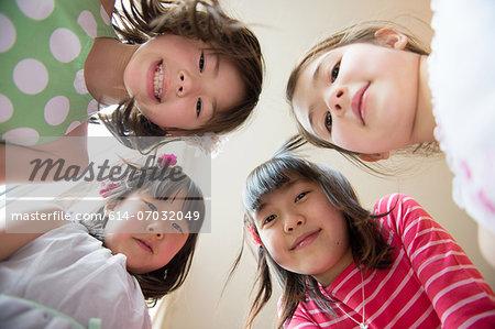 Girls in huddle looking at camera, smiling