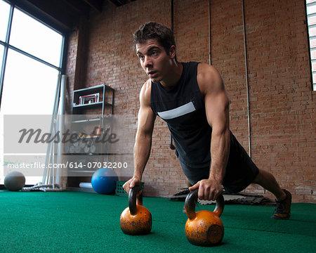 Male bodybuilder using kettlebells