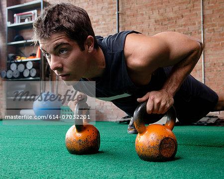 Male bodybuilder doing press up using kettlebells